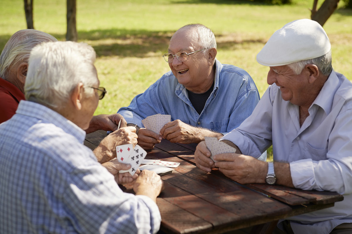 Happy Seniors Playing Cards Outside
